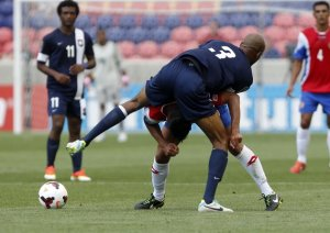 Belize's Trevor Lennen shelters another Tico from the burden of expectation. (image: sports.yahoo.com)
